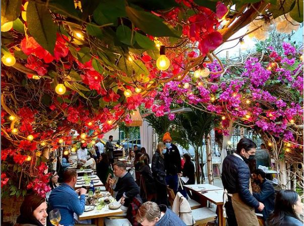 Outdoor seating at NYC restaurant laden with flowers overhead